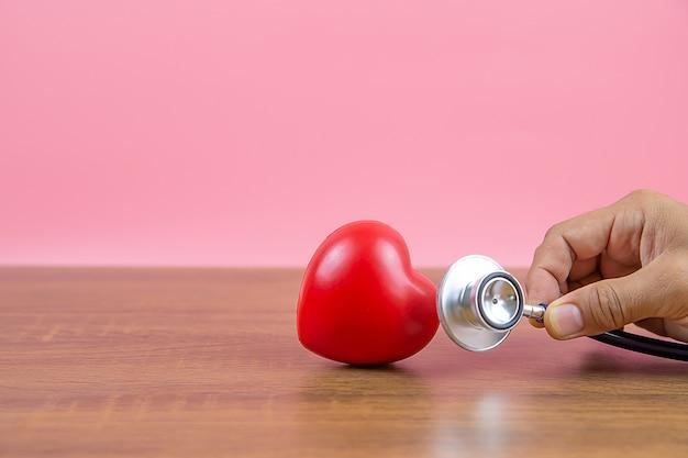 Bouchent la main à l'aide d'un stéthoscope vérifie un cœur.