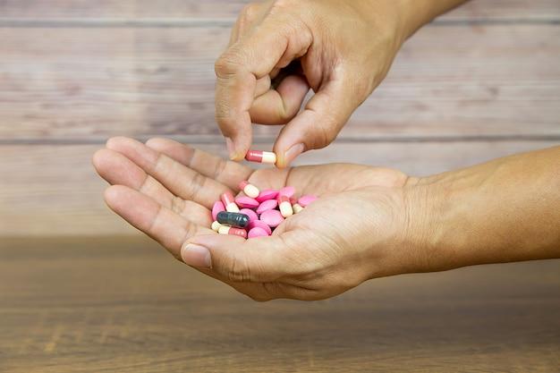 Bouchent la main choisissez une capsule de médicament.