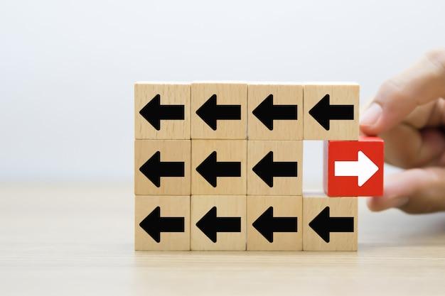 Bouchent la main choisissez la flèche sur des blocs de jouets en bois empilés.