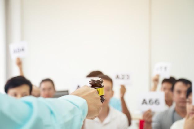 Bouchent la main du commissaire-priseur, tenant un marteau, un marteau en bois et un groupe de personnes floues