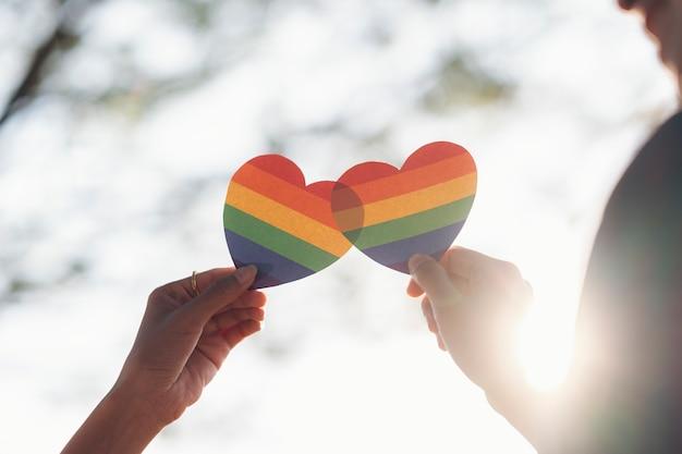 Bouchent la main du couple lgbtq tenant le coeur arc-en-ciel.
