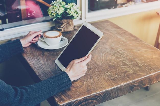 Bouchent la main femme à l'aide de tablette au café-restaurant avec ton vintage.