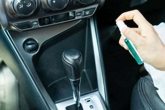 Bouchent la main de femme désinfectant le levier de changement de vitesse en pulvérisant de l'alcool à partir d'une bouteille, protection contre les virus infectieux, les bactéries et les germes. coronavirus / covid-19, concept de soins de santé.