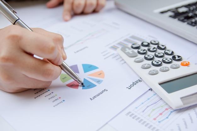 Bouchent la main femme tenant un stylo pointant sur le graphique du rapport de synthèse et calculent les finances