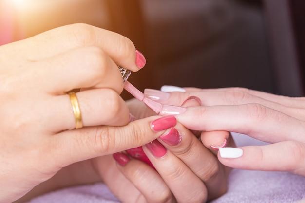 Bouchent la main de la femme tout en processus de manucure