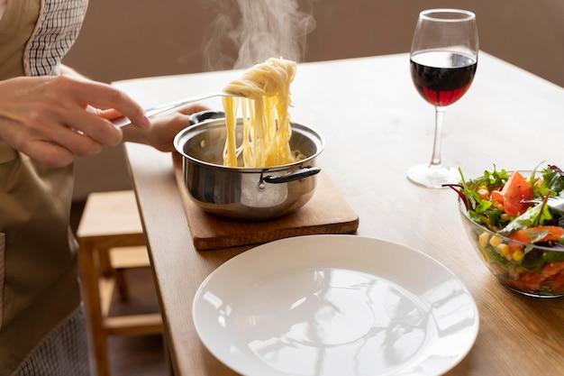Bouchent la main avec une fourchette tenant des pâtes