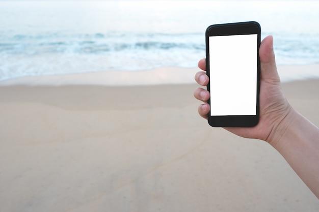 Bouchent la main de l'homme sur un smartphone noir sur beau fond bleu et calme de la mer et la plage.