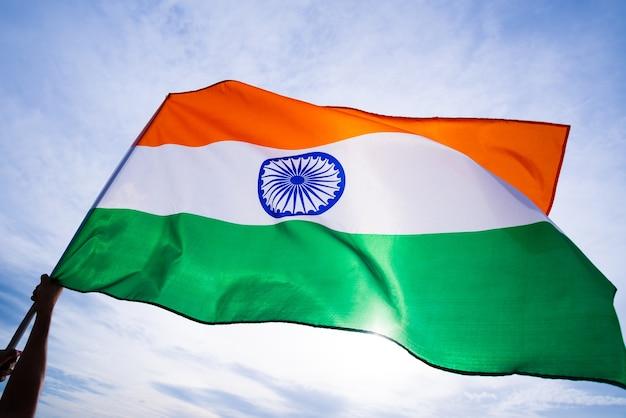 Bouchent la main de l'homme tenant le drapeau de l'inde sur le fond de ciel bleu.