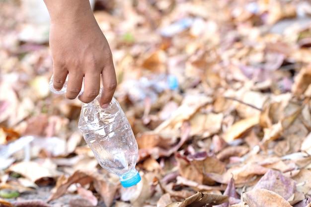 Bouchent la main ramasser une bouteille d'eau en plastique. sauver l'environnement et combattre la pollution plastique.