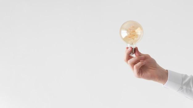 Bouchent la main tenant l'ampoule avec espace copie