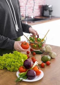 Bouchent la main tenant un bol avec une salade savoureuse
