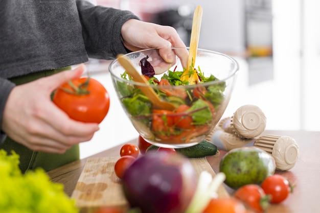 Bouchent la main tenant un bol avec de la salade