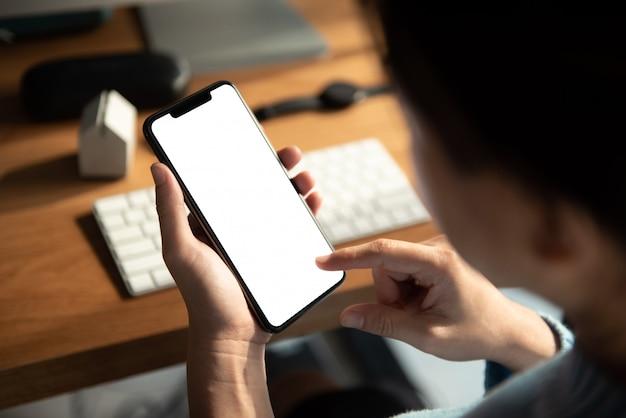 Bouchent la main tenant l'écran blanc de téléphone noir