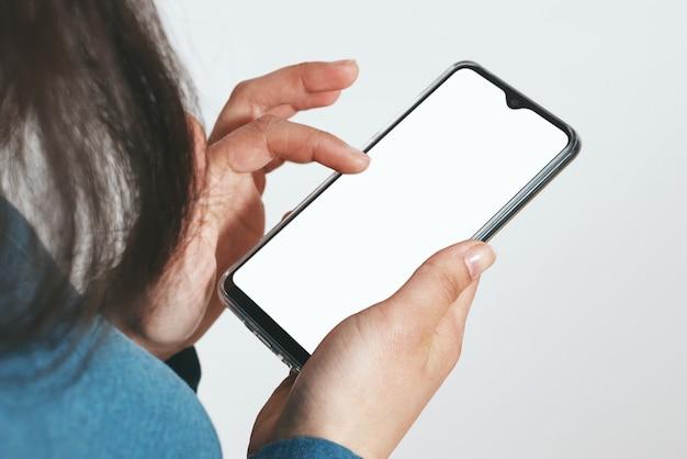 Bouchent la main tenant un téléphone noir sur un tracé de détourage blanc à l'intérieur.