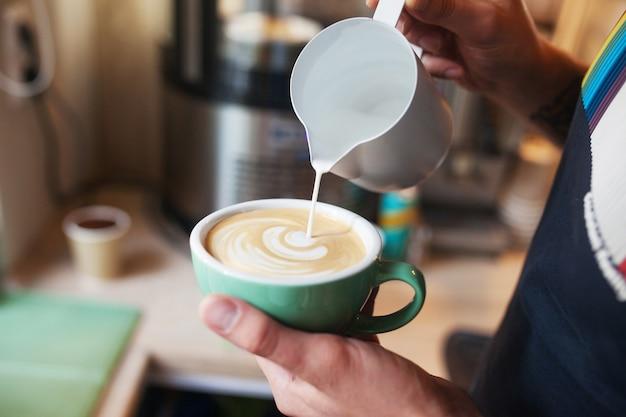 Bouchent les mains de barista versant du lait chaud dans une tasse de café pour faire de l'art de latte.art de latte de café professionnel dans un café.