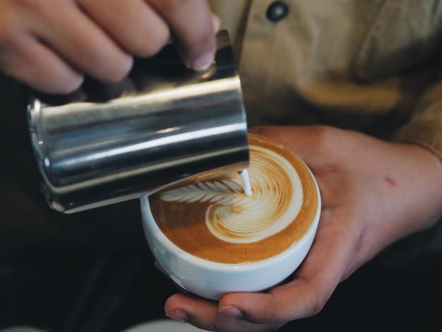 Bouchent Les Mains De Barista Versant Du Lait Chaud Pour Faire De L'art Latte. Photo Premium
