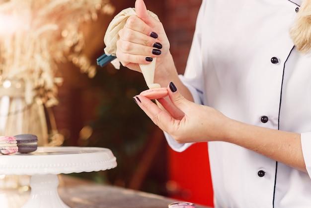 Bouchent les mains du boulanger avec un sac de confiserie en serrant la crème aux coquilles de macarons.
