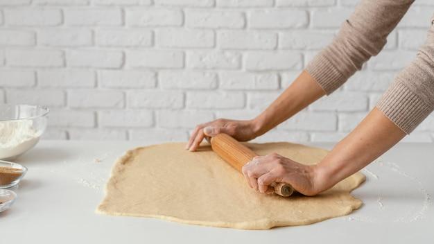 Bouchent les mains étalant la pâte