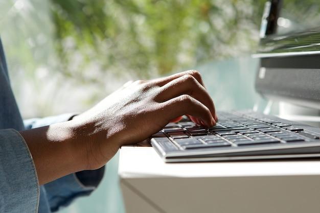 Bouchent les mains féminines sur le clavier d'ordinateur portable