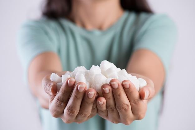 Bouchent les mains de femme tenant des cubes de sucre blanc. concept de soins de santé.