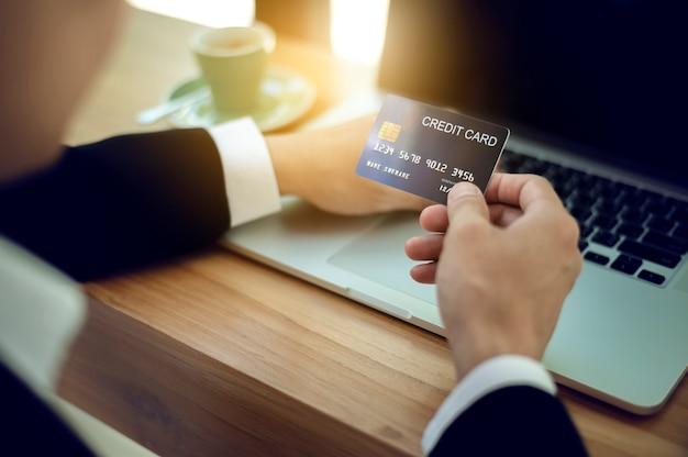 Bouchent les mains d'homme d'affaires détenant une carte de crédit et à l'aide de laboratoire pour effectuer le paiement en ligne. concept de magasinage en ligne.