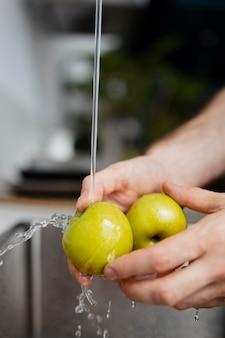 Bouchent les mains lavant les pommes
