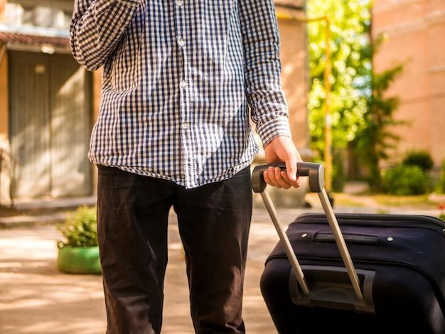 Bouchent les mains de personne touristique détiennent une grosse valise dans la rue en voyage d'été