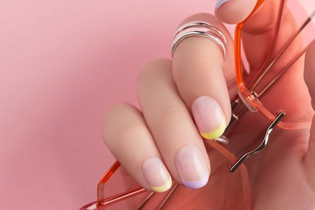 Bouchent les mains de womans manucurées sur fond rose