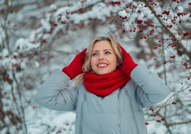 Bouchent naturel jeune fille blonde bouclée souriante dans la forêt enneigée.