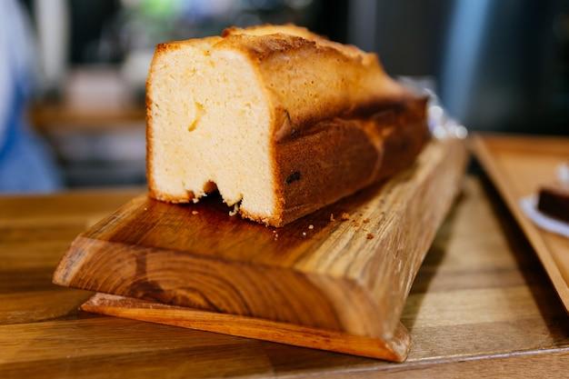 Bouchent le pain au beurre blanc fraîchement cuit sur une boîte en bois.