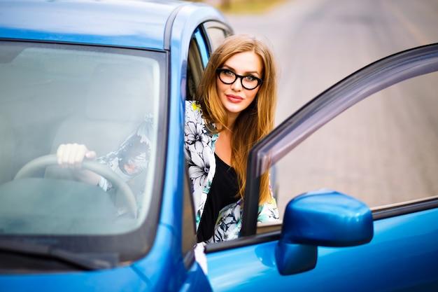Bouchent la photo de voyage de mode de vie en plein air de femme jeune hipster blonde au volant de voiture, lunettes et vêtements lumineux, grand sourire de bonne humeur, profitez de sa belle journée, jeune femme d'affaires