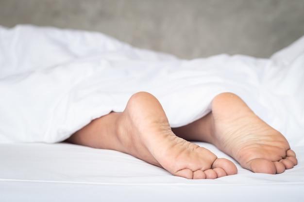 Bouchent les pieds des femmes sur la literie blanche au matin