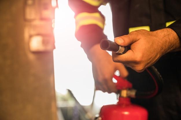 Bouchent pompier à la main à l'aide d'extincteurs de combat.