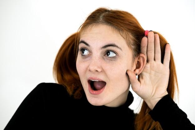 Bouchent le portrait d'une adolescente jolie rousse tenant une main à son oreille en écoutant un secret.
