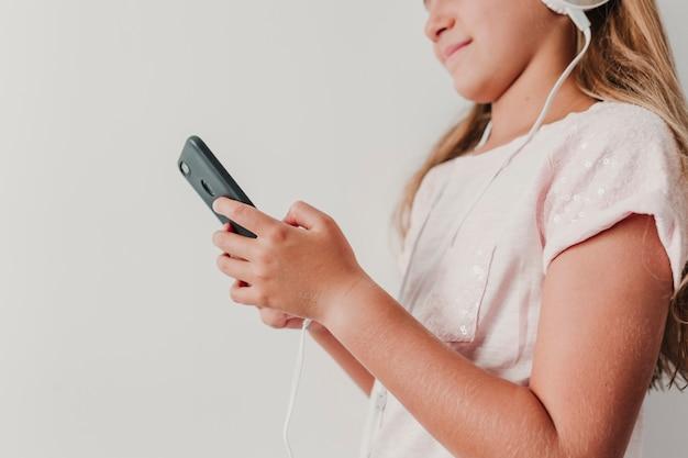 Bouchent portrait d'une adolescente mignonne joyeuse, écouter de la musique dans le téléphone mobile et les écouteurs.