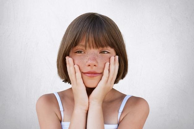 Bouchent le portrait de l'adorable fille aux taches de rousseur avec une coiffure flottante, gardant ses mains sur les joues, ayant une expression rêveuse, rêvant de nouveau jouet ou de vacances sur la mer. petit enfant au look réfléchi