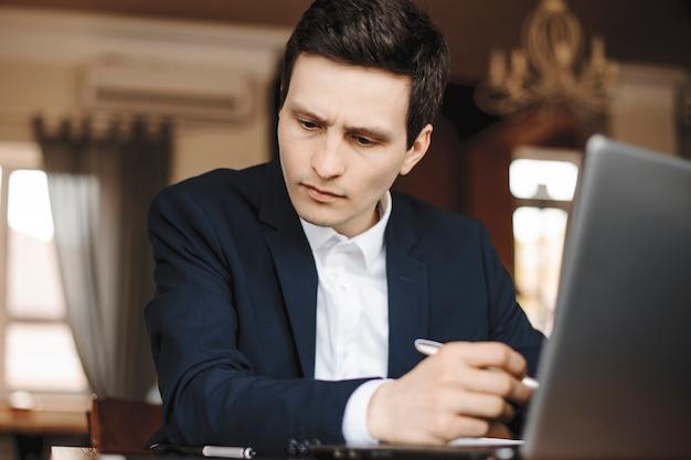 Bouchent le portrait d'un beau jeune designer travaillant assis dans un café.