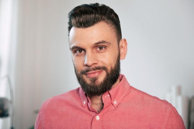 Bouchent le portrait d'un beau jeune homme confiant élégant barbu dans la chemise à la maison alors qu'il regarde la caméra
