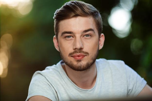 Bouchent portrait de beau jeune homme confiant en t-shirt blanc sur la nature extérieure floue