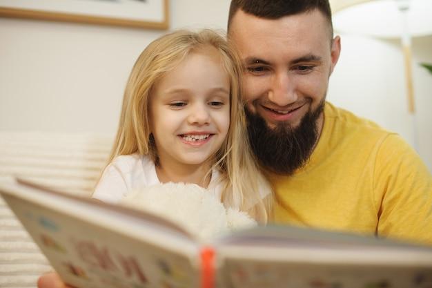 Bouchent le portrait d'un beau jeune père barbu lisant un livre avec sa fille à la maison le matin pendant que la mère travaille.