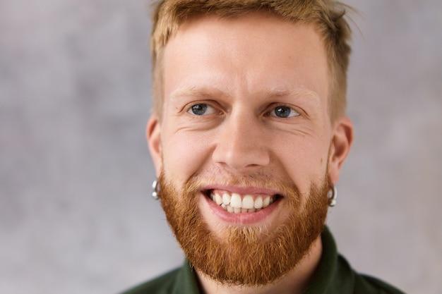 Bouchent le portrait de beau mec hipster européen élégant avec une nouvelle coupe de cheveux fraîche et une barbe touffue riant impuissant en regardant la comédie drôle, posant isolé. concept de joie, de plaisir et de positivité