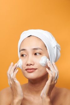 Bouchent le portrait de beauté d'une belle femme asiatique à moitié nue qui rit appliquant une crème pour le visage et regardant loin isolée sur fond orange