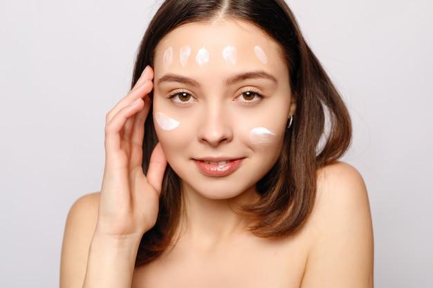 Bouchent le portrait de beauté d'une belle femme à moitié nue qui rit appliquant une crème pour le visage et regardant loin isolé sur fond blanc