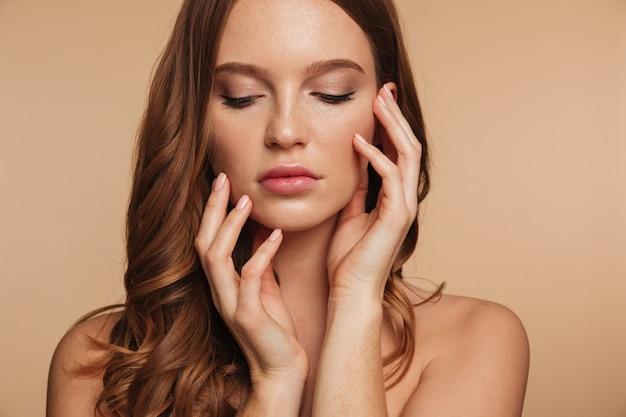Bouchent portrait de beauté de femme sensuelle au gingembre aux cheveux longs posant avec les bras près du visage