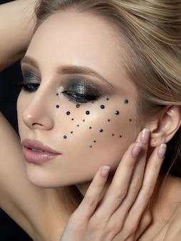 Bouchent le portrait de beauté de la jeune femme avec un beau maquillage de mode touchant son visage. maquillage de mode moderne. cils longs, yeux charbonneux bronze, strass noirs.