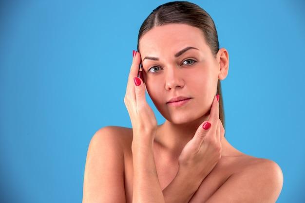 Bouchent le portrait de la beauté de la jeune femme brune souriante et touchant son visage sur le mur bleu. perfect fresh skin. concept de jeunesse et de soins de la peau.
