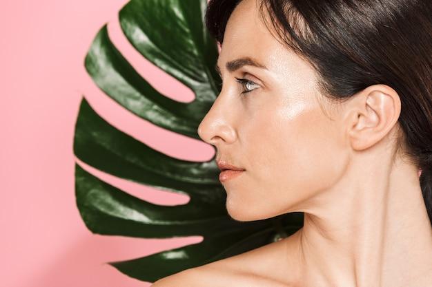 Bouchent le portrait de beauté d'une séduisante femme aux seins nus brune sensuelle debout isolée, posant avec une feuille tropicale verte