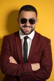 Bouchent le portrait de bel homme d'affaires à lunettes de soleil et costume bordeaux