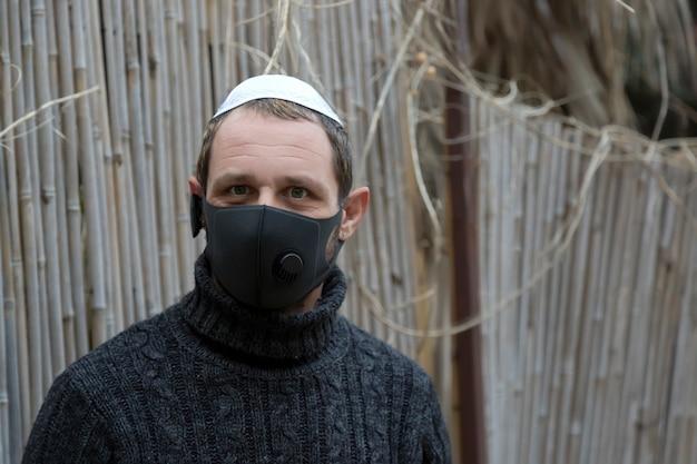 Bouchent le portrait d'un bel homme juif adulte portant la kippa et un masque facial noir