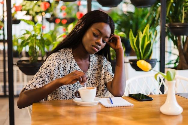 Bouchent le portrait d'une belle femme afro-américaine souriante avec une tasse de café